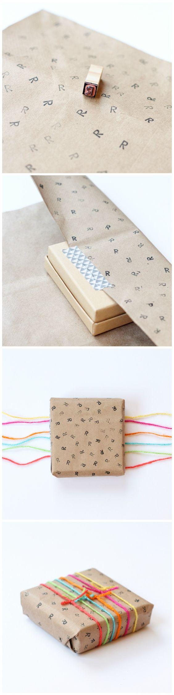 Envoltorios de paquetes o empaquetados para regalos en navidad con sellos de letras de fondo e hilos de colores.