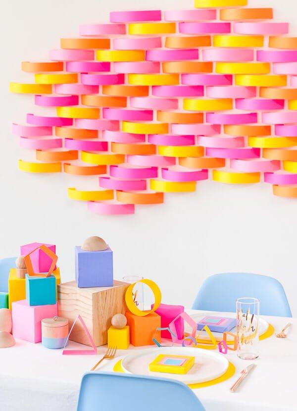 Mural de tiras de papel y centro de mesa con figuras geométricas de papel