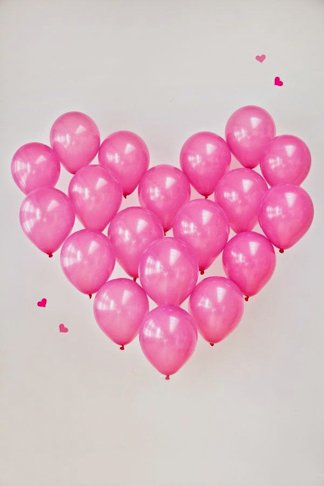 Decoracion romantica para momentos especiales como san valentin o bodas con grlobos rosas formando un corazon