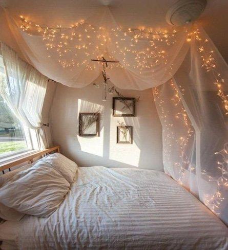 Decoracion romantica para momentos especiales como san valentin o bodas creando una cueba o mausoleo con telas y luces de navidad sobre la cama