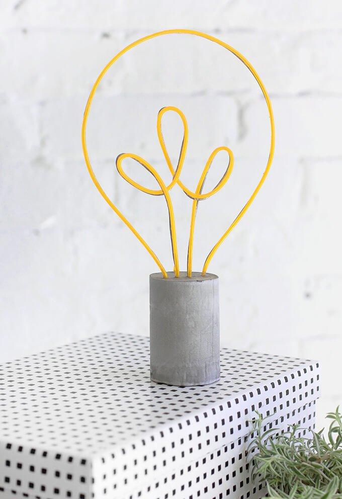 lampara de cemento e hilo de neon con forma de bombilla