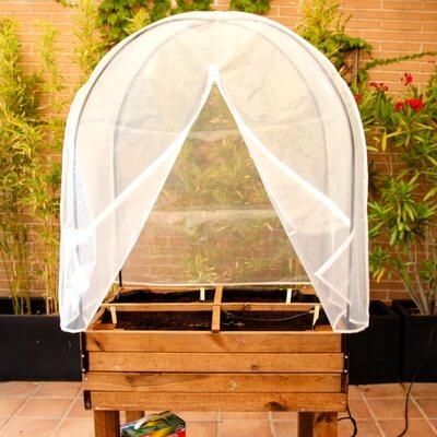 Mesa de huerto urbano de madera con invernadero