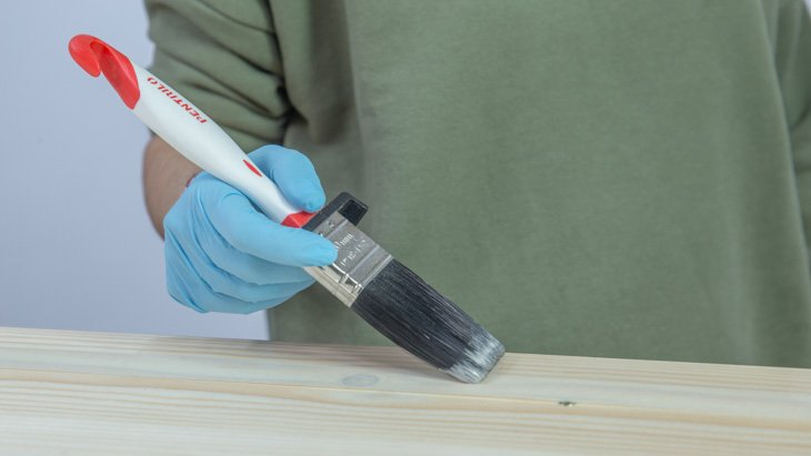 Aplicación del barniz decorativo sobre el cabecero de madera