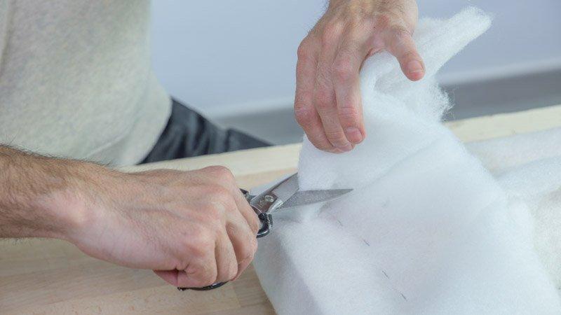 Tijeras cortando la guata que sobra después de tapizar el banco de madera