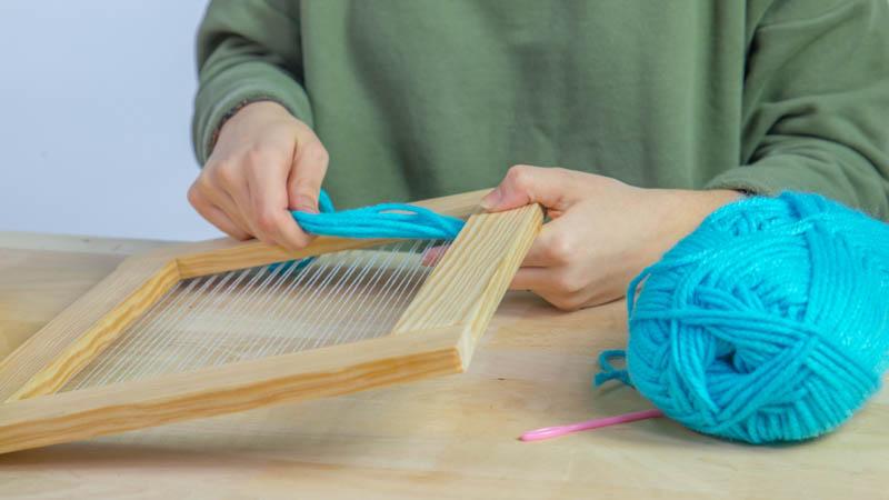 Creación de nudos con lana en el inferior del telar