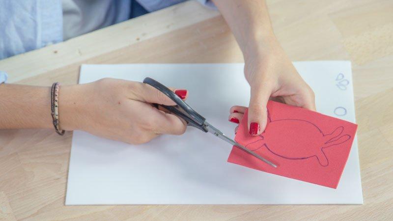 tijeras cortando la siluete de un cangrejo para hacer una marioneta de goma eva