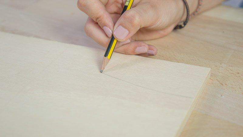 Lápiz dibujando las piezas en la madera