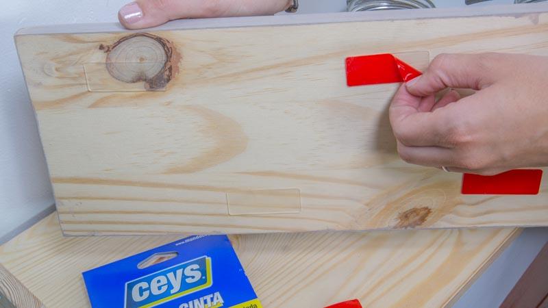 Apliación de una cinta de doble cara para pegar el estante de botes a la pared