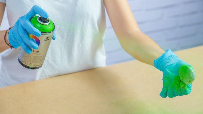 Aplicación de la pintura en spray sobre las piedras para hacer cactus DIY