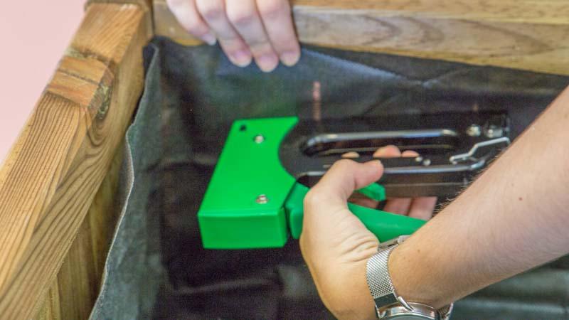 Grapadora manual fijando la tela geotextil