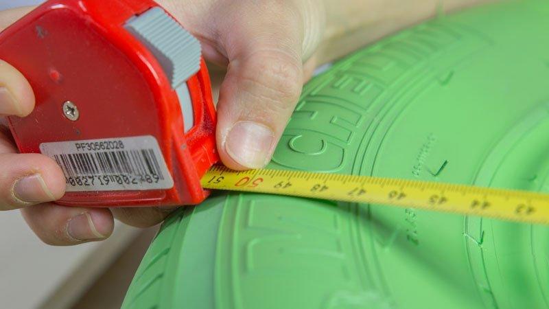 Flexómetro midiendo el diámetro del neumático