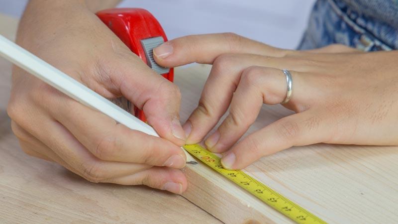 Uso del flexómetro para marcar la medida del neumático en la madera
