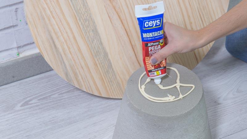 Aplicación de adhesivo de montaje para montar la mesa de cemento y madera