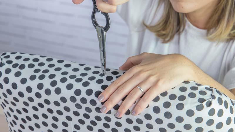 Tijeras abriendo agujeros en la tela para poder montar la silla después