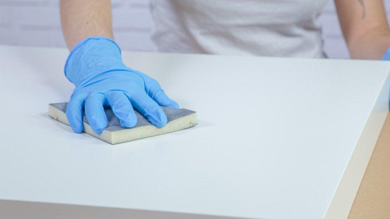 Taco de lija preparando la superficie de la mesa antes de pintar