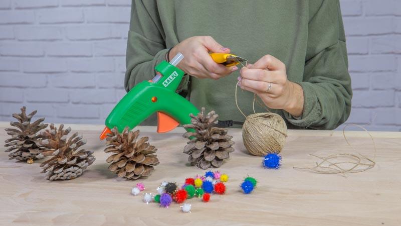 Colocación de la cuerda para hacer adornos navideños con piñas y pompones