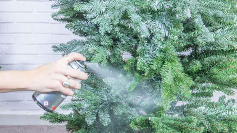 Pintura en spray adornando un árbol de Navidad