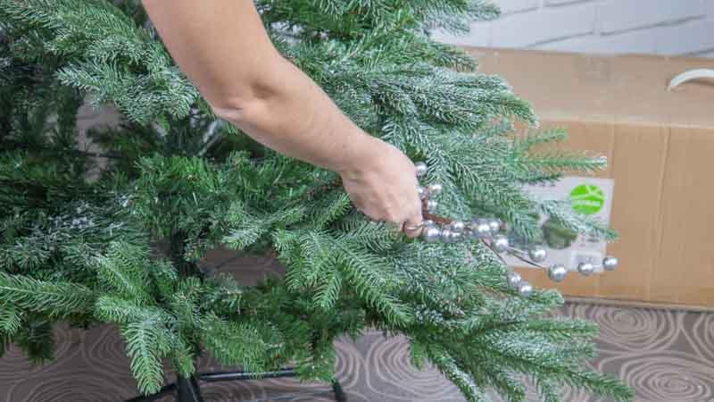Colocación de adornos plateados en el árbol