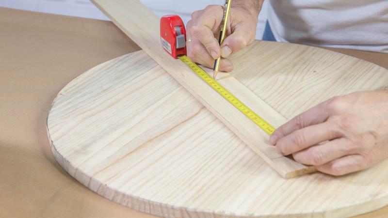 Lápiz trazando una base de madera en un tablero