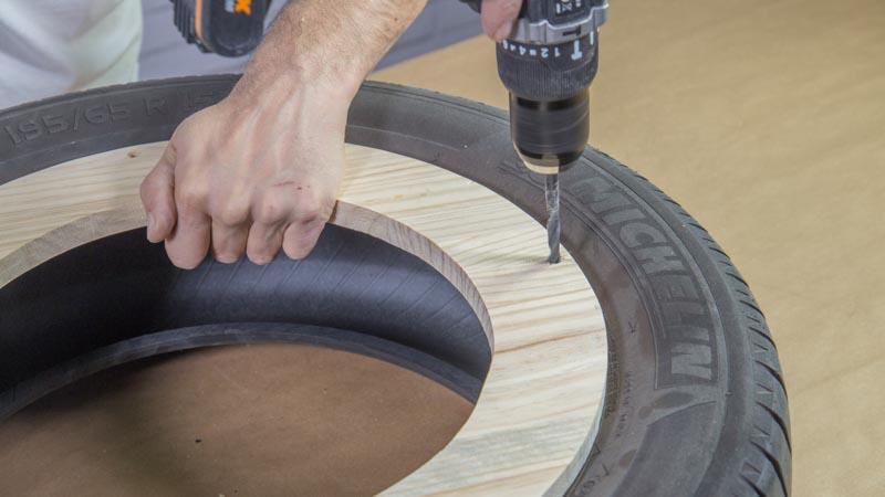 Taladro haciendo los agujeros en la madera para poder unirla al neumático
