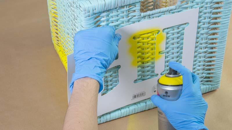 Decoración de una cesta de ratán con una letra usando un spray en base agua y una plantilla