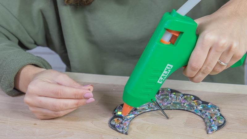 Pistola termoencoladora pegando las piezas