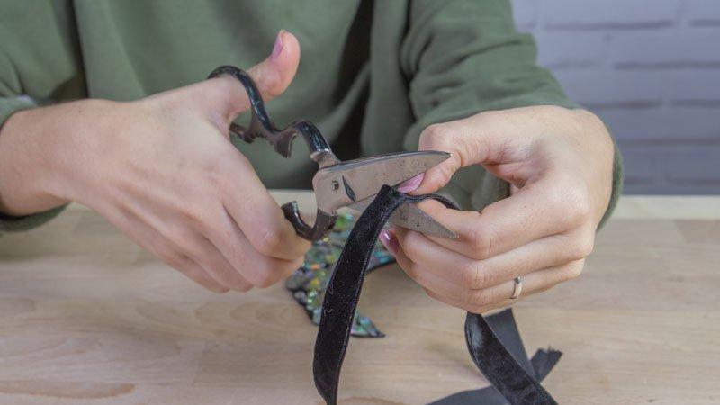 Tijeras cortando las tiras para poder colgar el collar
