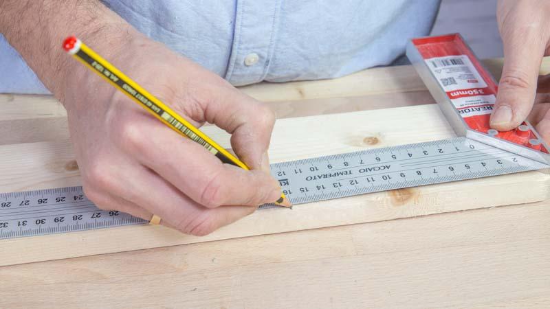 Lápiz marcando las piezas de los sujetalibros en la madera