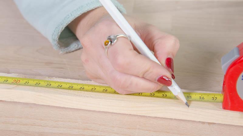 Rotulador marcando los listones de madera que formarán la estructura de la lámpara