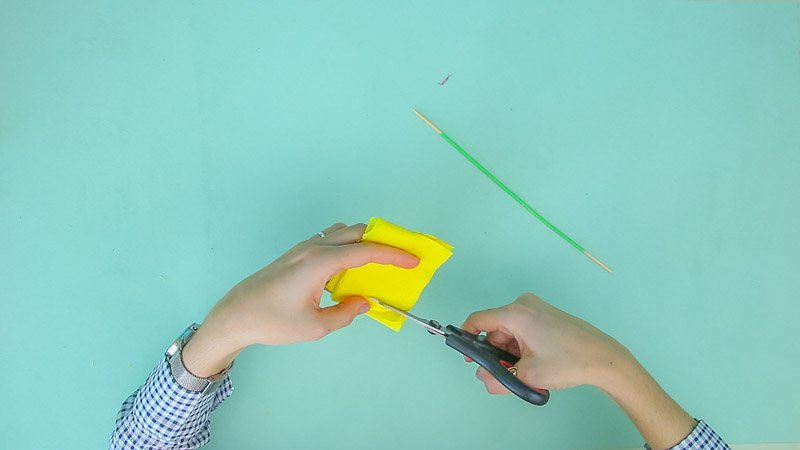Tijeras cortando el papel de seda para hacer flores amarillas