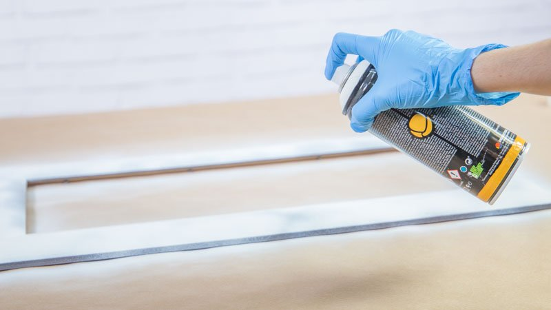 Aplicación de una imprimación en spray sobre el marco de madera