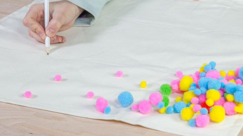 Pompones de colores sobre la funda básica de cojín