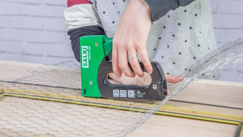 Grapadora manual fijando la malla de gallinero al marco de madera