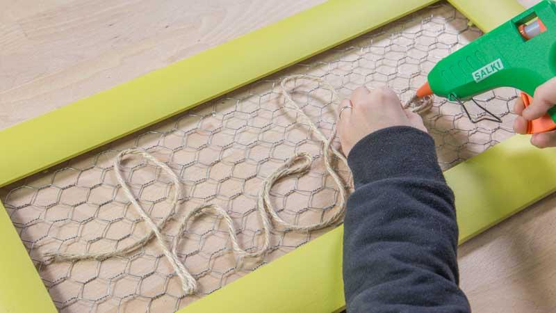 Pegado de la cuerda sobre la malla de gallinero para formar el mensaje