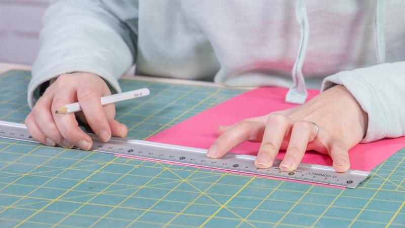 Lápiz dibujando sobre la cartulina para hacer la tarjeta