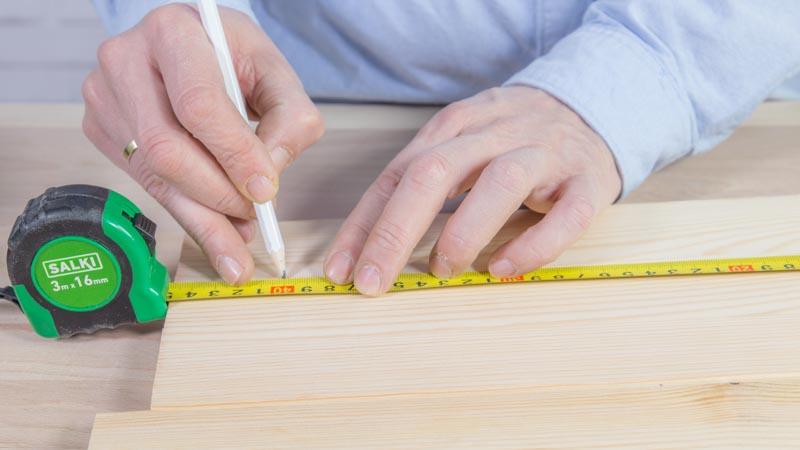Marcado de las piezas de madera con la ayuda de un flexómetor de Salki