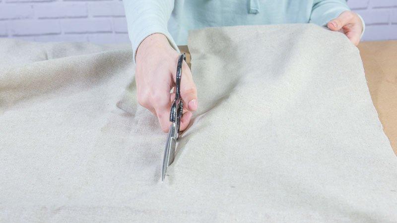 Tijeras cortando la tela que forma el revistero