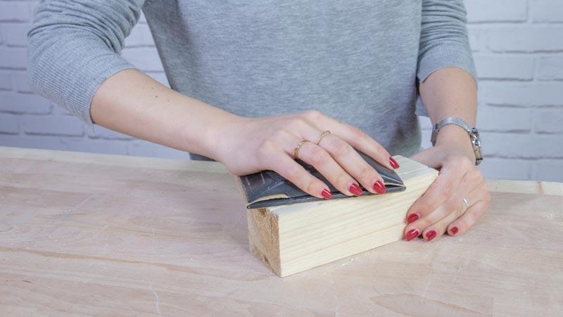 Lijado de las piezas de madera del adorno para las mesas de bodas