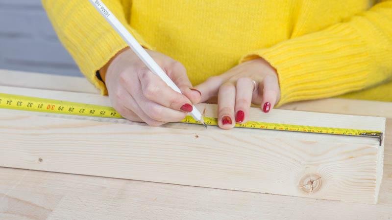 Lápiz marcando los listones de madera para hacer las piezas de la lámpara