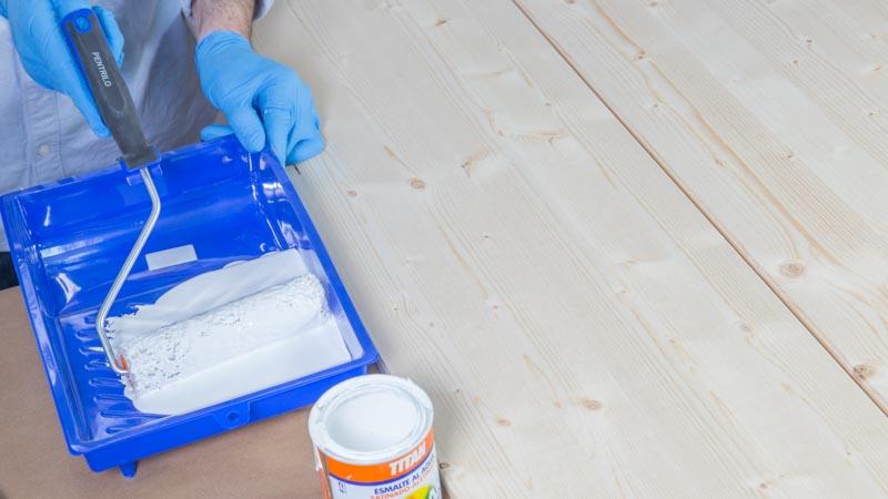 Rodillo y esmalte al agua blanco para pintar la madera