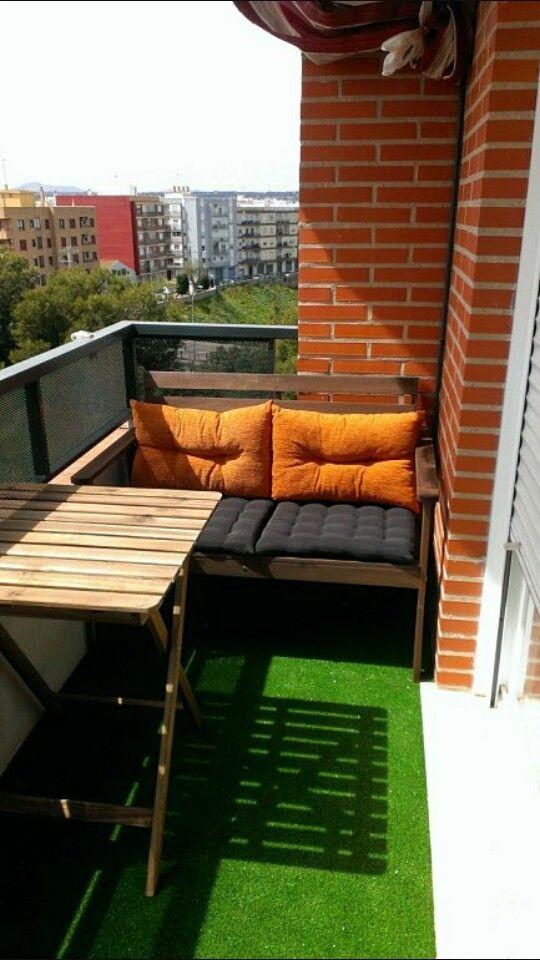 Terraza pequeña con césped artificial y muebles de madera