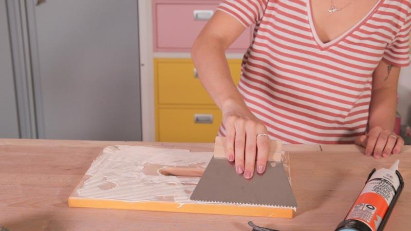 Espátula alisando el adhesivo para azulejos de baixens