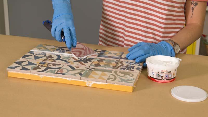 Aplicación de masilla para rellenar espacio entre azulejos