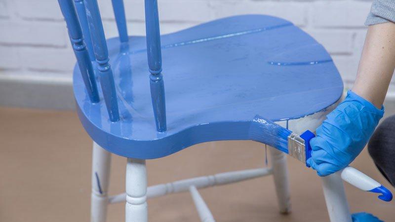 Aplicación de una pintura para exterior sobre una silla de madera