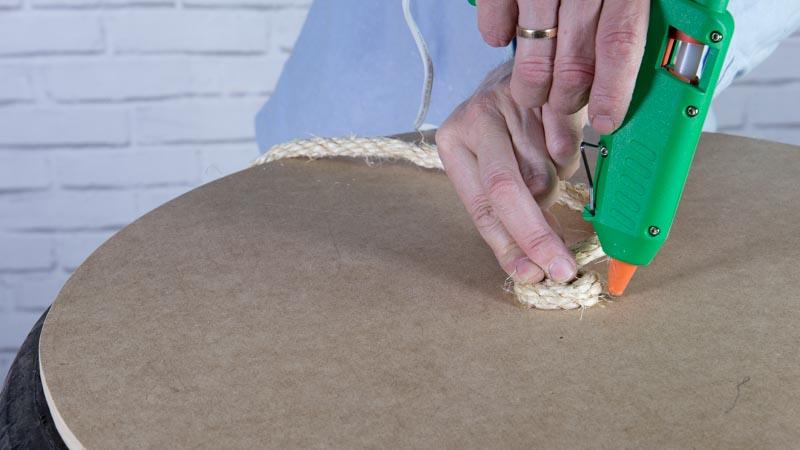 Pegado de la cuerda para decorar la mesa con un neumático