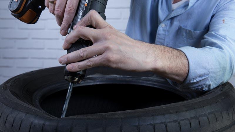 Taladro haciendo los agujeros en el neumático