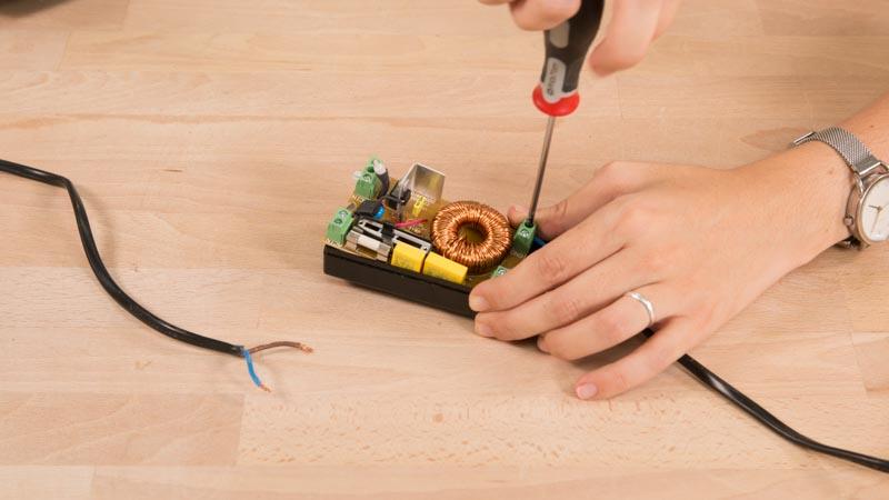 Destonillador apretendo la conexión de los cables en el regulador de intensidad