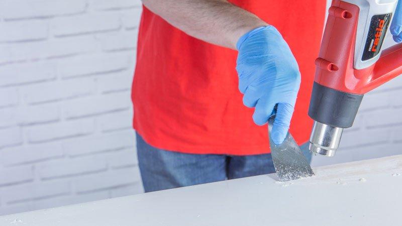 Retirar la pintura de un mueble con decapador y espátula