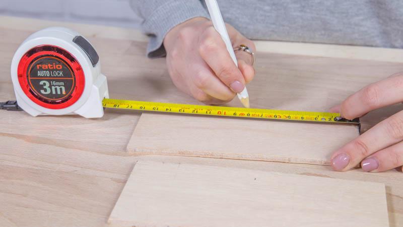Medir las piezas de madera de la caja con el flexómetro