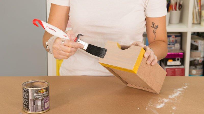 Paletina aplicando un barniz decorativo sobre los cajones de la cajonera
